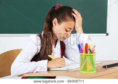 Beautiful little schoolgirl in classroom near blackboard