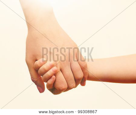 Child and mother hands together on light background
