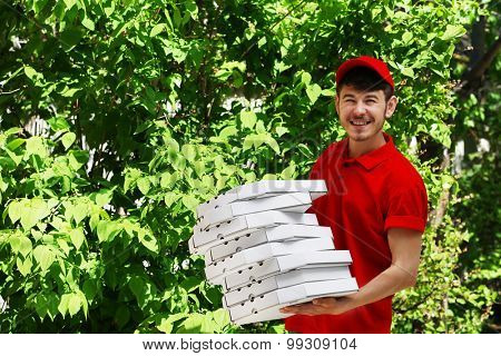 Delivery boy with cardboard pizza box, outdoors