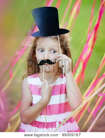 little girl with funny paper mustache and hat