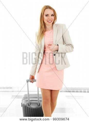 Woman holding suitcase in airport