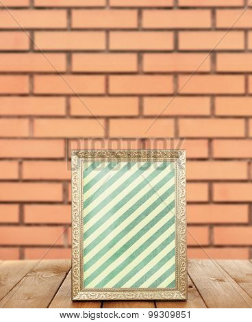 Photo frame standing on table on brick wall background