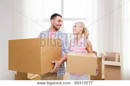 home, people, repair and real estate concept - smiling couple with big cardboard boxes moving to new place