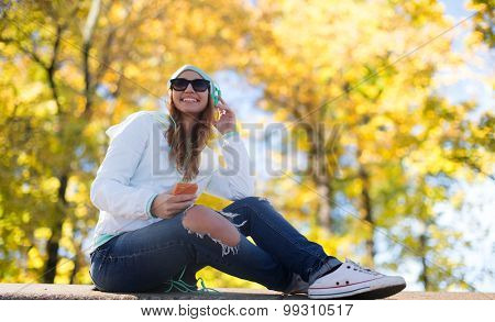 technology, music, season and people concept - smiling young woman or teenage girl with smartphone and headphones listening to music outdoors over autumn park background