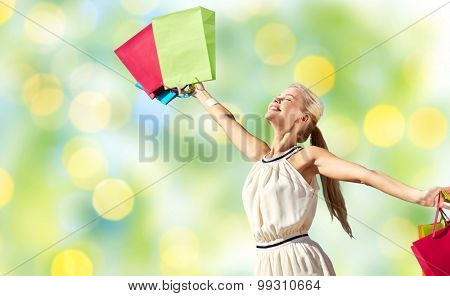 consumerism, sale and people concept - smiling woman with shopping bag rising hands over green lights background