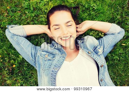 lifestyle, summer vacation, leisure and people concept - smiling young girl with closed eyes lying on grass
