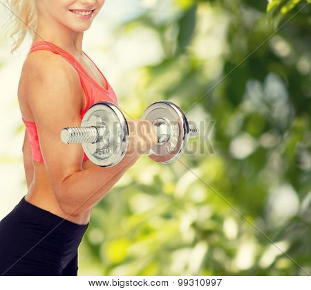 fitness, healthcare and exercise concept - close up of young sporty woman with heavy steel dumbbell