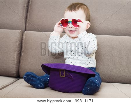 Caucasian baby boy hold glasses  sitting on sofa at home