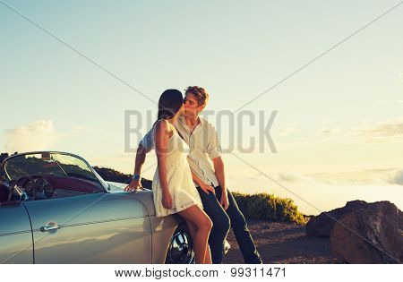 Romantic Young Attractive Couple Watching the Sunset and Kissing with Classic Vintage Sports Car
