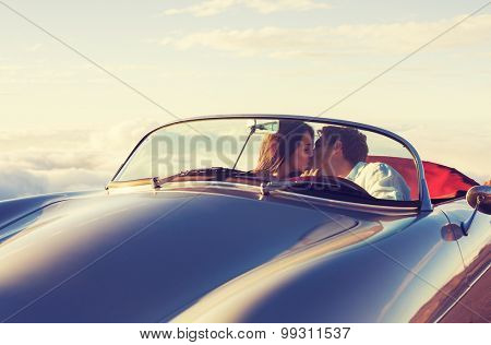 Romantic Young Attractive Couple Watching the Sunset and Kissing in Classic Vintage Sports Car