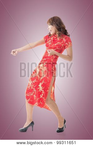 Chinese woman dress traditional cheongsam and pull something at New Year, full length portrait isolated.