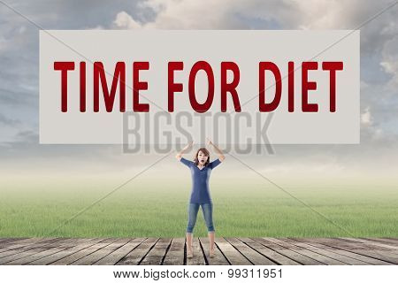 Time for diet, words on blank board hold by a young girl in the outdoor.