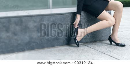 Business woman put on shoes after a break in the outside.