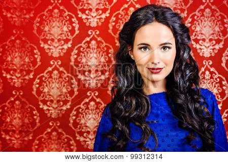 Portrait of a beautiful brunette woman in elegant evening dress posing over vintage background. Fashion shot. Hairstyle.