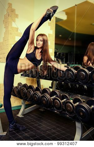 Slender girl doing stretching exercises at the gym. Active lifestyle, bodycare. Perfect figure.