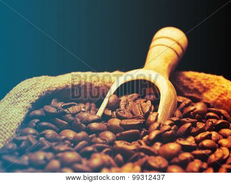 Coffee beans on burlap sack with wooden scoop.Filtered image: cool cross processed vintage effect.