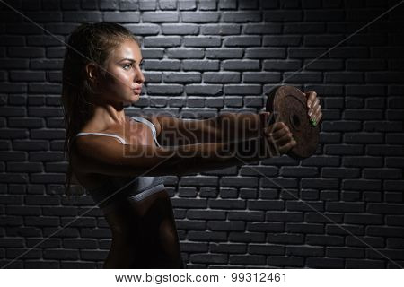 Young sexy woman doing a fitness workout with weights