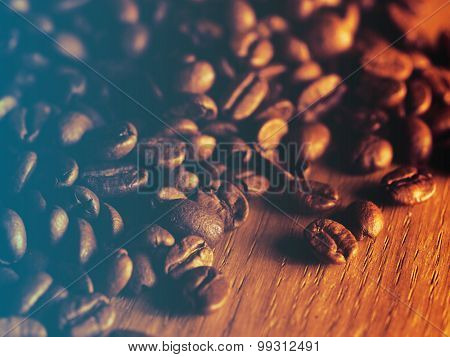 Fresh roasted coffee beans on wooden board.Filtered image: cool cross processed vintage effect.