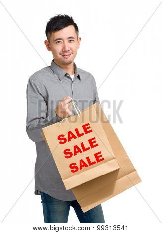 Asian man hold with shopping bag and showing three sale word