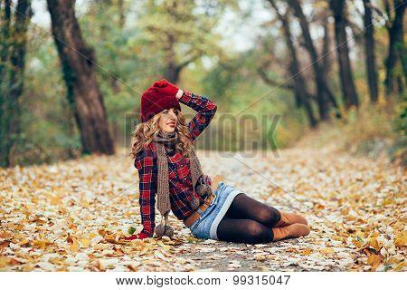 Beautiful Woman Sitting In Fallen Leaves