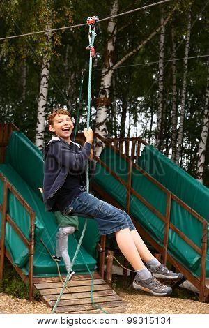 boy in  summer sport  park on cable railway attraction