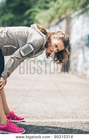 Woman Runner Leaning Over Stretching Out After A Run