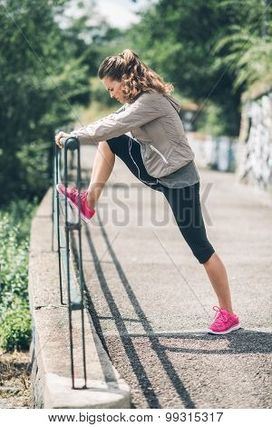 An Athletic Woman In Profile Stretching Out Against Guardrail