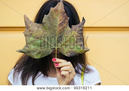 Young Woman Holding A Fallen Leaf In The Face During An Autumn Walk Outdoors