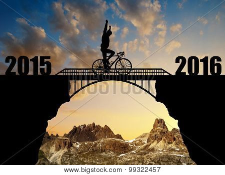 Cyclist riding across the bridge at sunset. Forward to the New Year 2016
