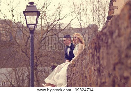 Bride And Groom Sitting On A Wall