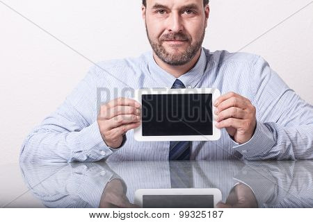 Business man on office desk showing tablet