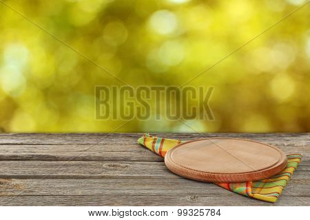 Wooden table with tablecloth and cutting board