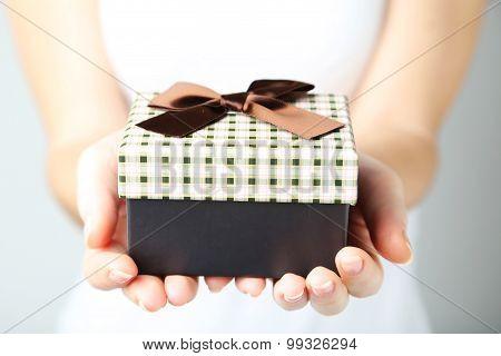 Female hands holding gift box