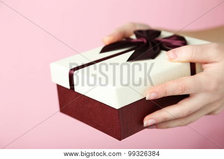 Female Hands Opening Gift Box On Pink Background
