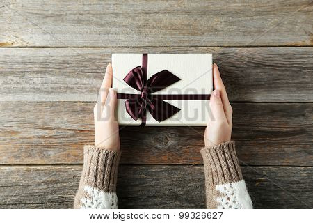Female Hands Holding Gift Box On Grey Wooden Background