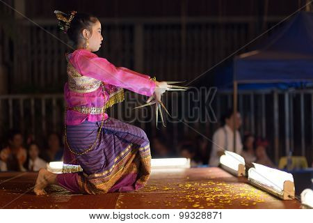 CHIANG MAI, THAILAND, JANUARY 04, 2015: A woman is performing a free Thai traditional dance in the street during the weekly Saturday night street market in Chiang Mai, Thailand
