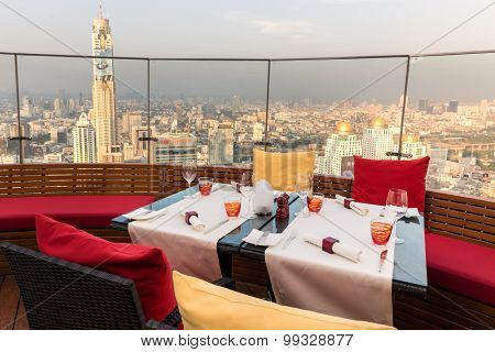 BANGKOK, THAILAND, JANUARY 14, 2015: Restaurant table with view on the Baiyoke tower and cityscape at the Red Sky Rooftop of the Centara hotel in Bangkok, Thailand.