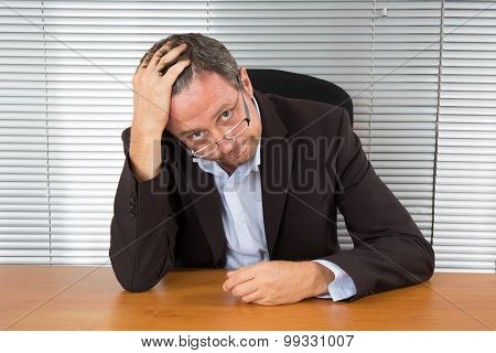 Too Much Work. Portrait Of Exhausted Businessman Sitting At Office Desk