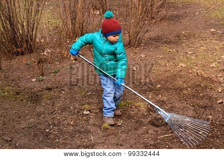 little boy cleaning spring lawn