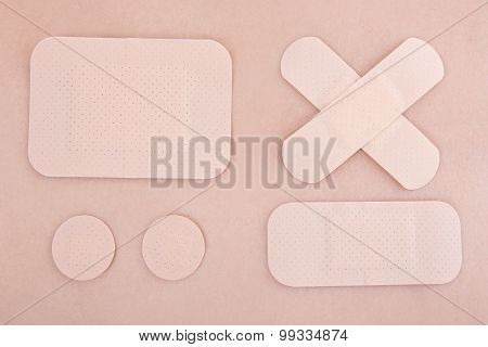 Different Medical Adhesive Plasters On Skin Background