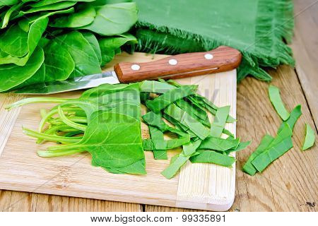 Spinach shredded with knife on board