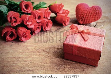 Rose With Red Gift Box And Red Heart Shape On Wooden Table