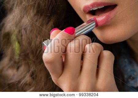 Young Woman Applies Lipstick Close-up
