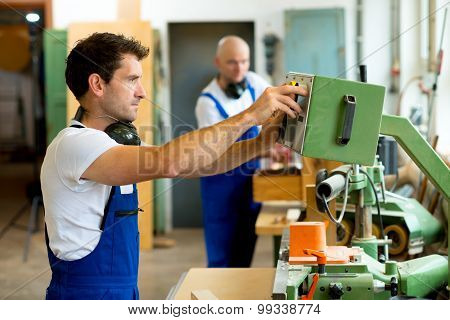 Worker In Factory Using Machine