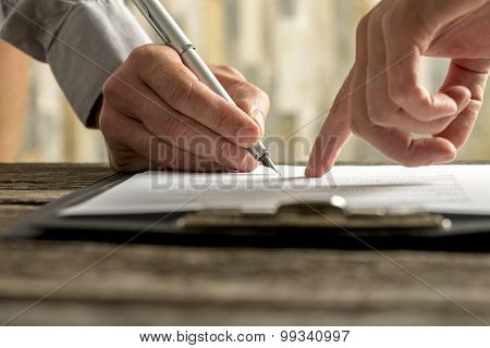 Closeup Of Employer Showing His New Employee Where To Sign An Employment Contract
