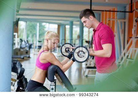 young sporty woman with trainer exercise weights lifting in fitness gym