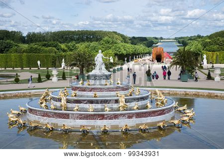 Visitors In Garden Palace Versailles With Statue And Pond At Paris, France