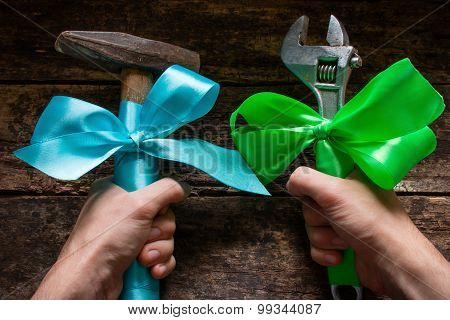 Worker Holding Adjustable Wrench And A Hammer Tied With Festive Ribbons In Labor Day