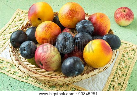 A Lot Of Plums, Apples And Nectarines In A Wicker Basket