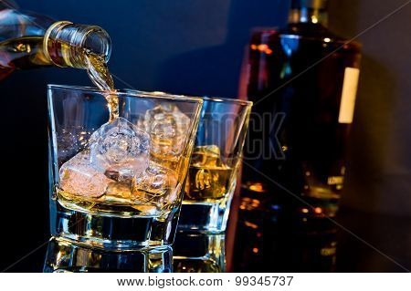 Barman Pouring Whiskey In Two Glasses With Ice Cubes On Table With Light Tint Blue And Reflection